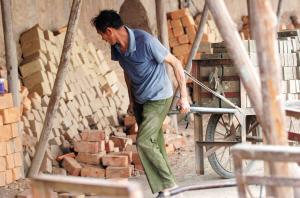 砖工们每天的工作就是把两条长40多米的砖墙用人力车拉到窑洞里面。