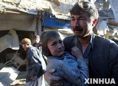 资料图片:3月14日,在阿富汗首都喀布尔发生爆炸的武器市场,一名从残骸中搜救出的儿童与父亲相拥而泣。(来源:新华社)