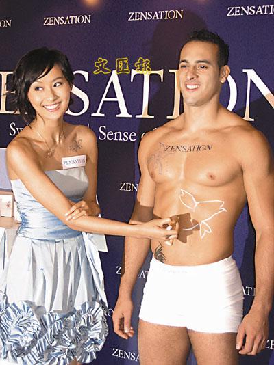 陈法拉在男模特儿身上画上图案,表情尴尬。