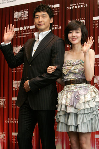 South Korean actress Lim Su-jeong (R) and actor Jung Ji-Hoon, also known as Rain, wave during a news conference in Hong Kong March 19, 2007. The gala premiere of their movie