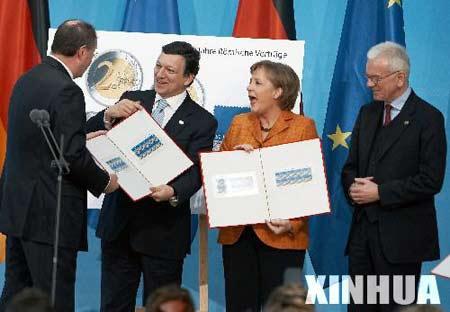 3月25日,在德国首都柏林,德国总理默克尔(右二)、欧盟委员会主席巴罗佐(左二)从德国财政部长施泰因布吕克(左一)手中接过欧盟50周年纪念邮票