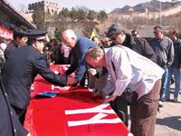 日前,城管队员在八达岭长城宣传市容环境整治工作,外国友人签名支持