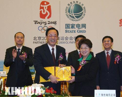 2006年1月26日,北京市副市长、北京奥组委执行副主席刘敬民(左二)代表北京奥组委向国家电网公司副总经理陈月明赠送纪念品。当日,北京奥组委与国家电网公司在京签署合作协议,国家电网公司成为北京2008年奥运会电力供应合作伙伴。 新华社记者孟永民摄