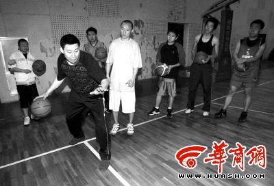 篮球训练基地总教练李仁(左)向体验者讲解篮球知识