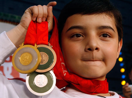 Chinese child performer Aerfa from Xinjiang displays Beijing Olympic medals after the medal launching ceremony in Beijing March 27, 2007. The launching of the medals coincided with the 500 day countdown to the Olympic Games in China's capital which will fall on August 8, 2008.