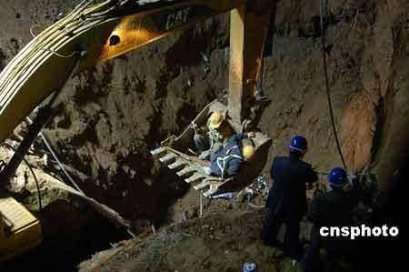 3月29日凌晨,两位抢险施工人乘挖掘机装载斗下入塌方坑底。北京地铁10号线工程二标段苏州街车站东南出入口发生塌方事故,塌方面积约20平方米,深度11米,施工单位中铁12局有六名施工人员被埋土中。接报后,北京市委、市政府负责人高度重视,立即组织营救,确保人员安全。 中新社发 廖攀 摄