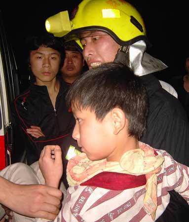 昨日凌晨,抚州市沿河路56号老五皇殿布匹市场突发大火,消防官兵救出一名孩子。记者舒晓燕摄