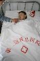 图文:小晖探望生病儿童 为小男孩盖棉被