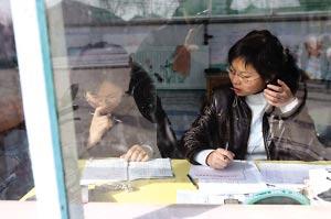 大学生村官李丰蓉(右)在村里跟同事一起工作。本报记者 刘军 摄
