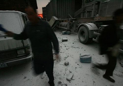 爆炸现场旁边工厂的工人从现场跑出。