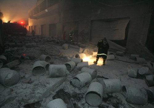 爆炸现场一片狼藉,变成一片白色,一名消防员在现场搜寻。