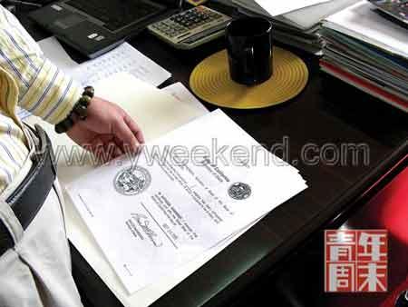 月1日,贺政在他的办公室内向记者展示基金会的证书拷贝件