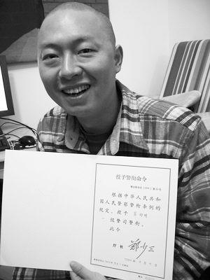 照片:吴幼明展示自己的一级警司授衔证书。周丽摄
