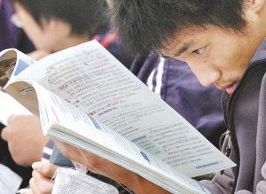 4月8日,在南京市第一中学考点,一名考生边复习边等候进场考试。 新华社记者 孙参摄