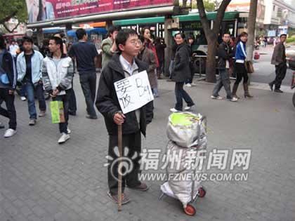 """8日下午,记者在鼓楼区东街口见到了这位胸前挂着""""要饭""""牌子的青年人——夏海波。"""