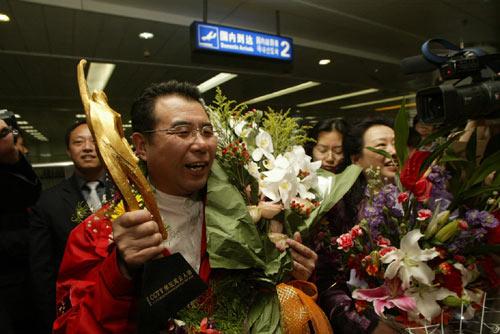 图文:王刚义获奖载誉归乡 手拿奖杯和鲜花