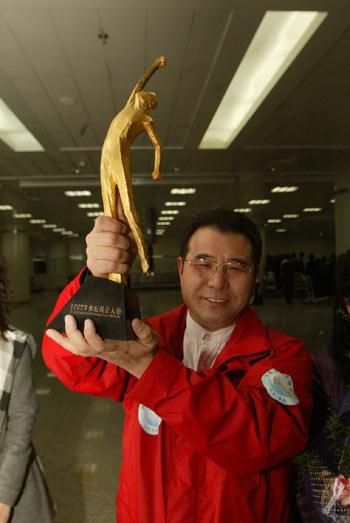 图文:王刚义获奖载誉归乡 高举小金人无比自豪