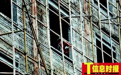 11:45  疯汉还在高楼处拿砖头往下扔,接着就被特警从身后制服。郭柯堂 摄