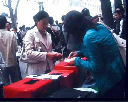 活动组织者表示,现场录像中的一位女子(左)曾拿着一张100元钞票前来募捐柜台上,要求只捐10元,工作人员找给了她90元