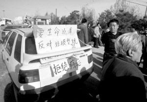 图为市民用汽车堵住填埋场的大门抗议。本报记者 张斌 摄