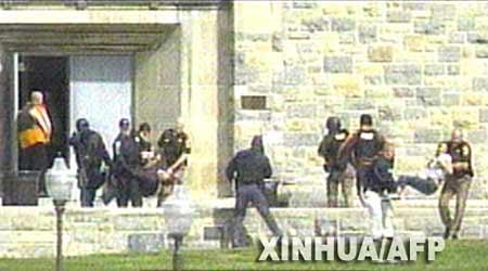 在这张4月16日拍摄的CNN电视台电视截图中,警察正在将学生从一栋楼中抬出。
