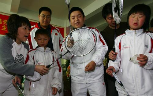 邓亚萍、孙海涛和孙俊正在教孩子们打羽毛球