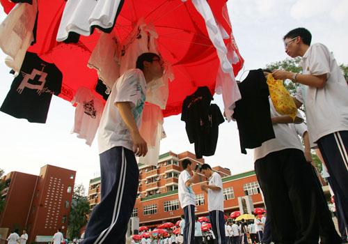 一位学生用太阳伞挂衣服叫卖