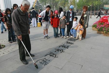 """玉渊潭公园门口老人在写""""奥"""""""