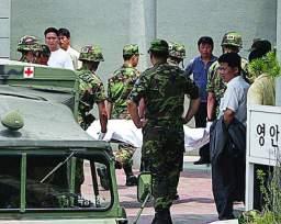 """2005年6月19日,韩国一所靠近""""三八""""线的军营内,一名新兵朝着营房内熟睡的战友先投掷一枚手榴弹,然后拿起步枪连开40多枪,造成8名士兵死亡、两人受伤。图为一名死亡士兵被抬往医院。新华社"""