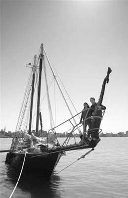 """里德和索尼娅站在""""安妮号""""纵帆船上,准备出海远航。"""