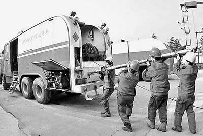 图①2005年12月2日,中国石化集团中原油田测井公司的工作人员在搬运设备,准备去中标的油井工作。