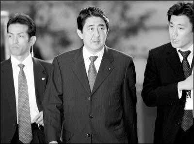 特警队员(左)警惕地守护在安倍首相(中)身旁