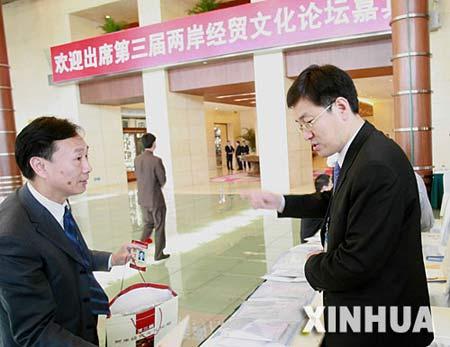 4月27日,参加第三届两岸经贸文化论坛的代表(左)在北京饭店签到。