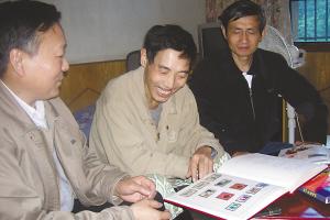 贾晓敏(中)与邮友黄治新(左)、杜宪明在翻阅珍藏的邮票