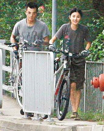 郑伊健、蒙嘉慧一起推着自行车