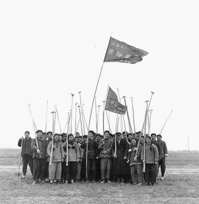"""1956年3月中旬,河南省开封县东方红农业生产合作社开展社会主义劳动竞赛。获得竞赛""""优胜红旗""""的青年们喜气洋洋地合影留念。本报记者洪克摄"""