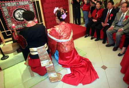 5月3日,新郎新娘行夫妻对拜礼。