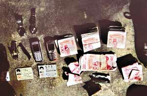 警方从犯罪嫌疑人身上收缴的部分赃款和赃物。