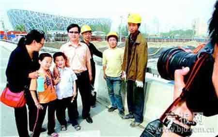 """昨天,从河南来京旅游的崔先生一家特意到北四环观看""""鸟巢"""",巧遇几位奥运工程建设者,崔先生邀请他们与家人一同合影留念。""""五一""""长假期间,许多外地游客选择参观建设中的奥运场馆。"""