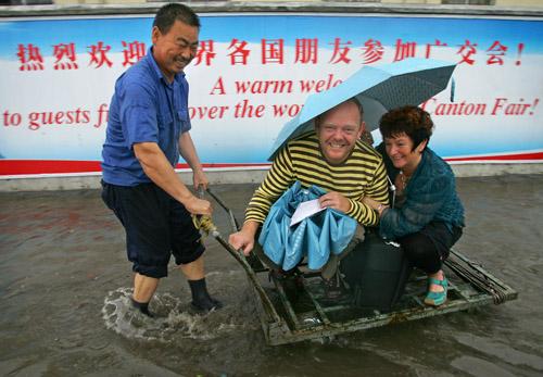 两个参加广交会的外国人正在体验中国特色的交通工具