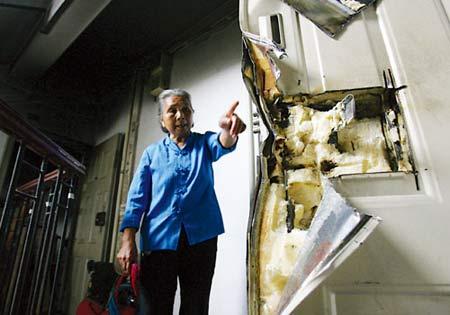 昨日,江北区小苑黄桷园,老人正述说自家防盗门在救火过程中被损毁的情况 记者 徐元宾