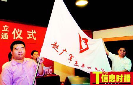 """4月19日,广州成立全国第一支以个人命名的青年志愿者服务队——""""赵广军志愿服务队""""。图为赵广军(左一)接过队旗。"""