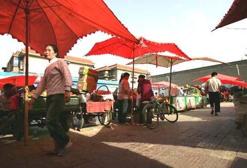 下午5时许,菜贩们重新撑起大遮阳伞