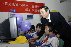 紫光股份总裁李志强在紫光电脑爱心体验活动中指导学生使用电脑