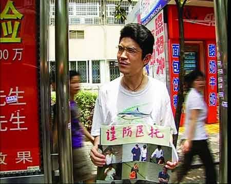 """5月18日,湘雅医院急诊科附近,邓志凌举着写有""""谨防医托""""四个字的牌子四处游走,提醒患者谨防上当。"""