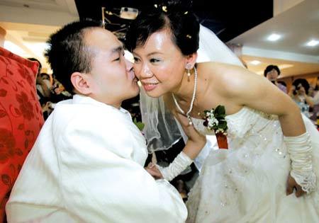 昨日,南岸残疾人服务中心,自强不息的残疾人丁胜奇与妻子在婚礼现场甜蜜相吻 记者 钟志兵 摄