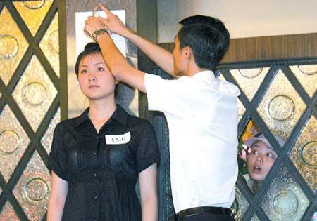 昨日,江北和府饭店,考官在给应聘者测量身高时,引来场外的参选者窥看 记者 钟志兵 摄
