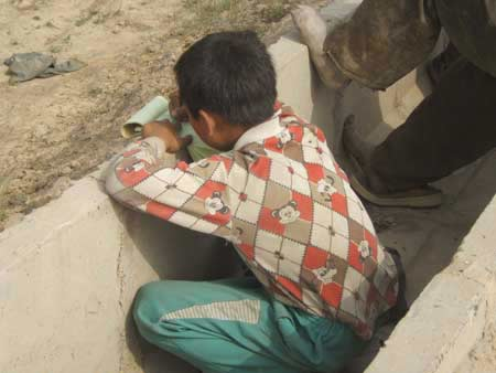 孩子无家可归,趴在水渠上写字