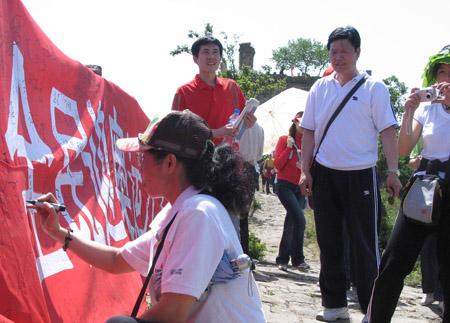 活动吸引众多旅游,他们兴致勃勃的参加签名活动,表达对奥运的深深祝福之情。