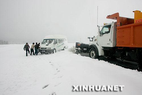 月22日,清雪车在新疆303省道哈密天山段清理积雪时与一陷在雪中汽车相遇